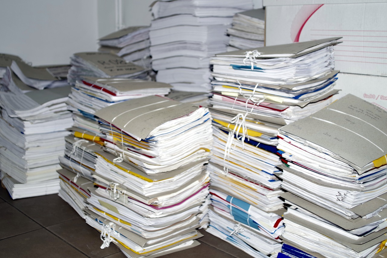 Stacks of folders and paper tied together, sitting on the floor.