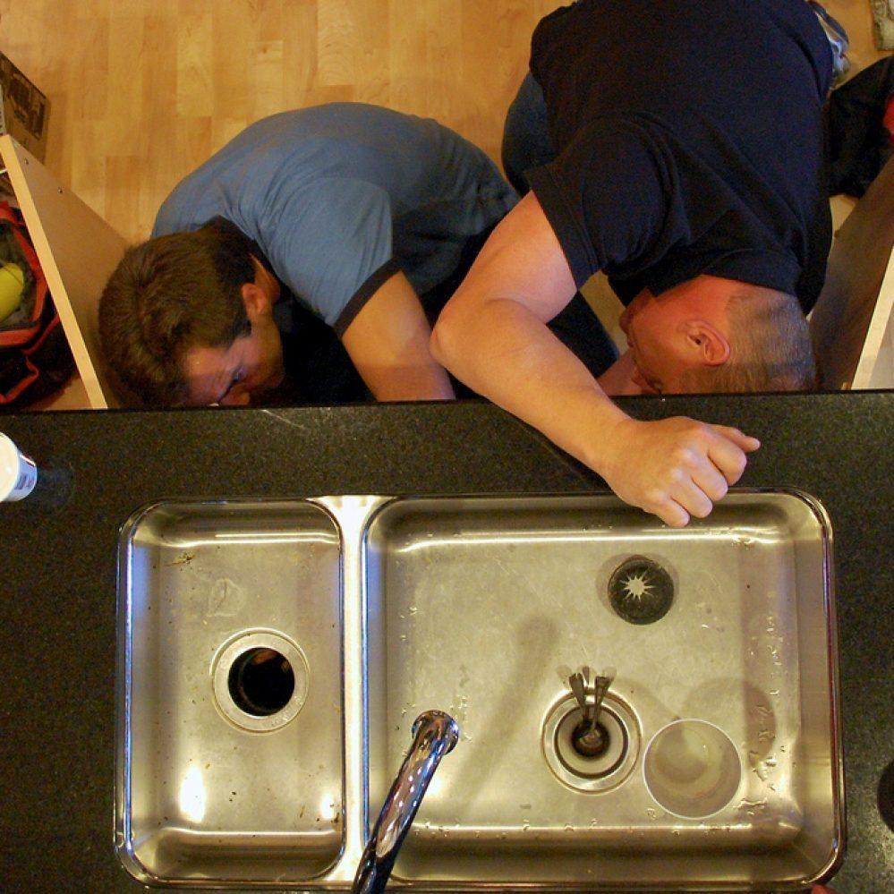 2 male plumbers working plumbing maintenance under kitchen sink