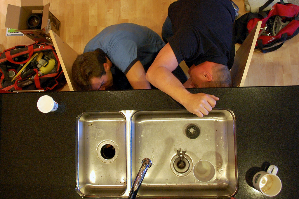 2 male plumbers working plumbing maintenance under kitchen sink