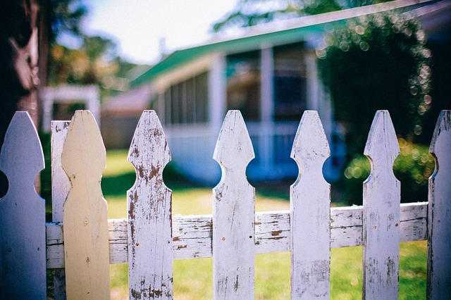A white picket fence separating two hours through a yard.