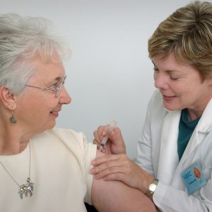Elderly woman receiving medicinal injection from senior health care professional