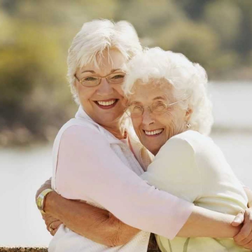 baby boomer daughter hugging elderly mother