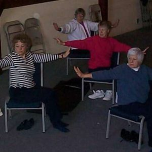 Seniors practicing holistic health and wellness in chair yoga class.