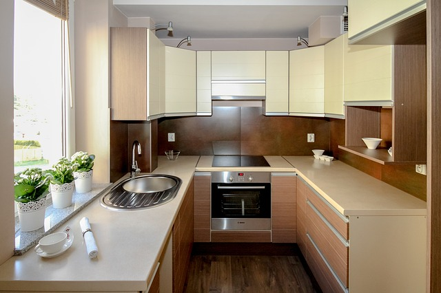 A small apartment kitchen with stove, cooktop, cabinets, and a large open window.