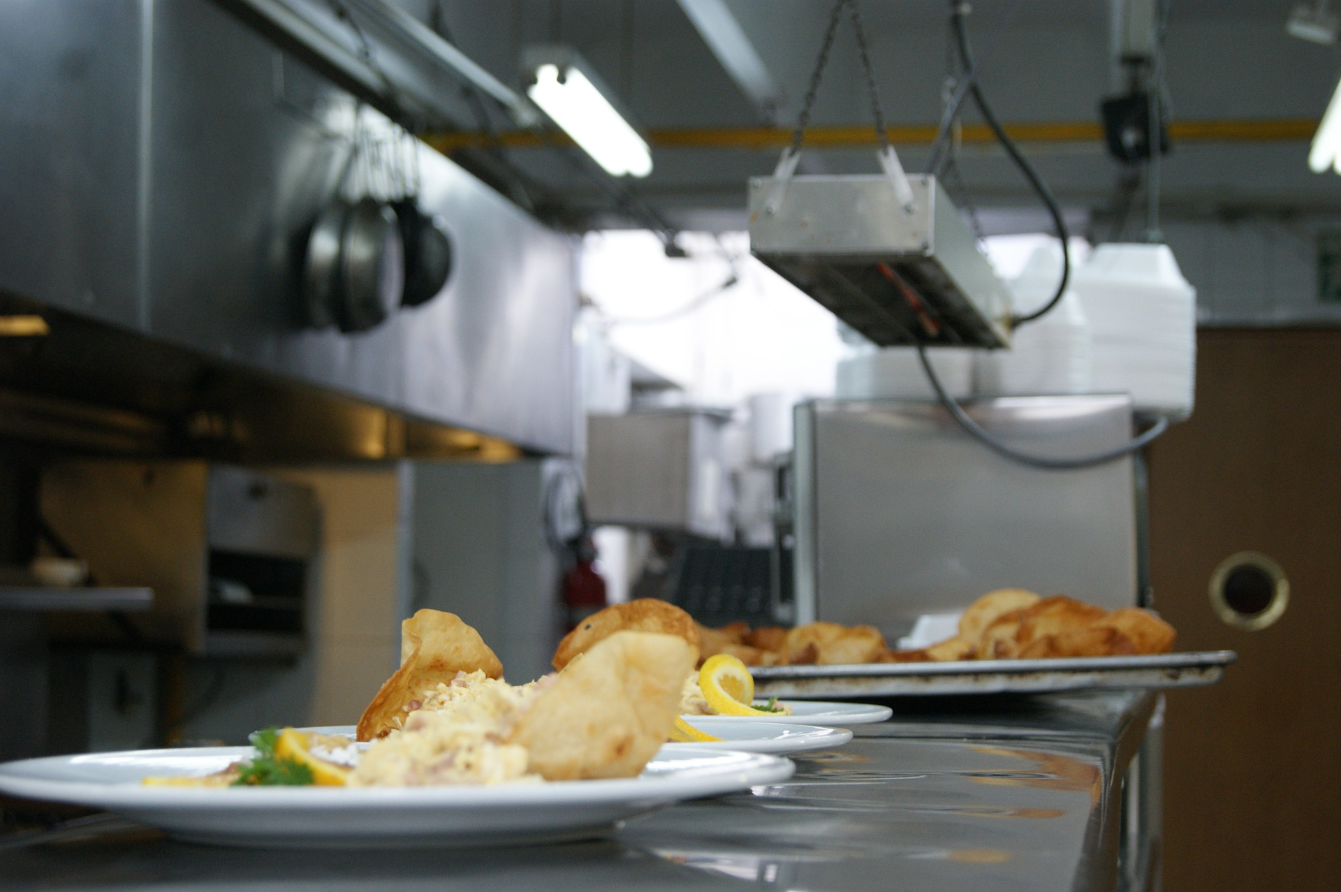 Prepared meals sitting on a counter under a food warmer in the kitchen of a restaurant.