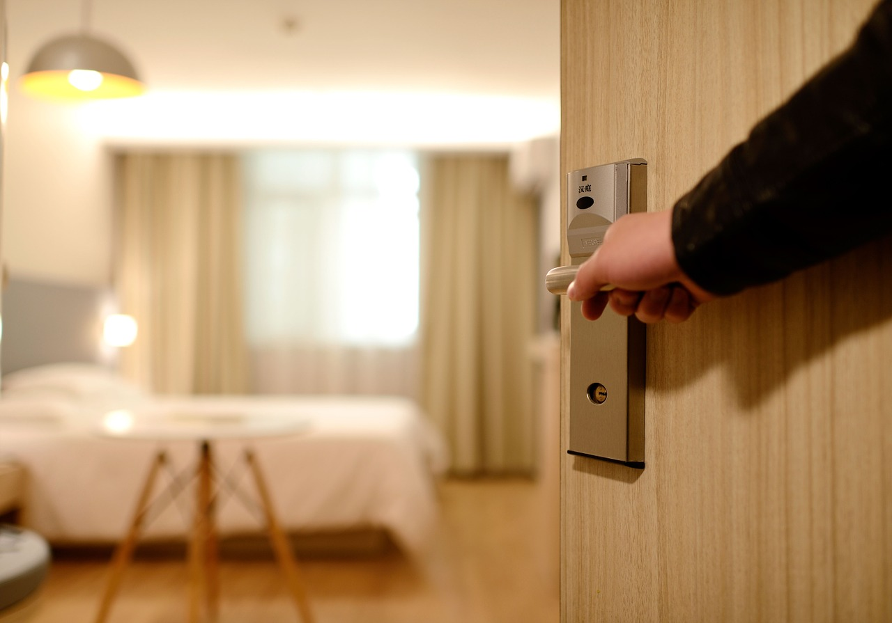 A man opening a hotel room door.