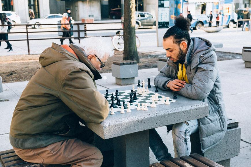 And older man and younger man sitting in a park, playing chess at a table.