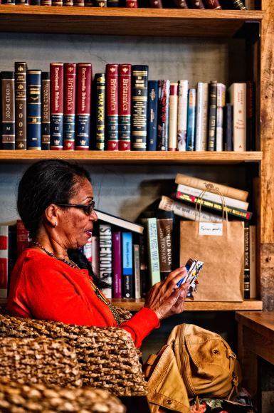 Older lady sitting in front of a bookshelf and reading something on her smartphone.