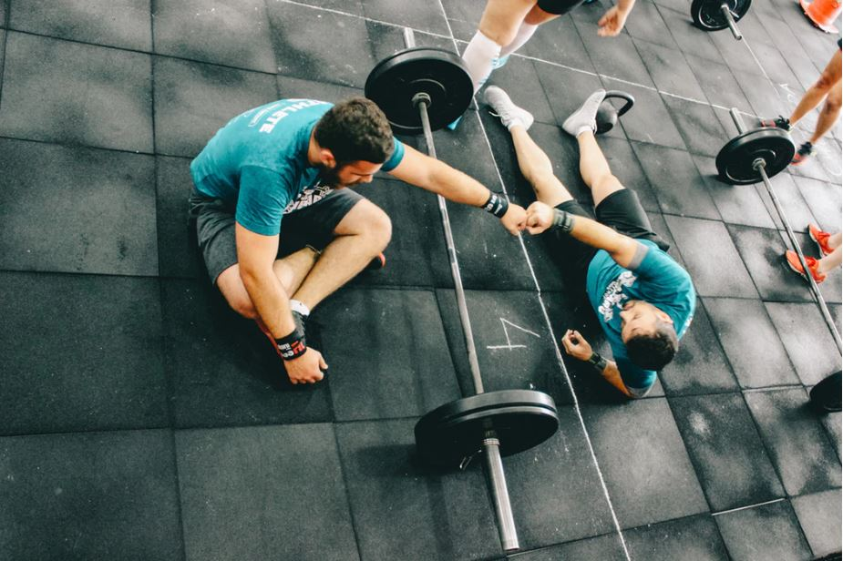 Two men sitting on a gym floor after lifting weights