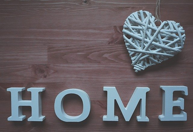 HOME in wooden block letters with a woven heart ornament