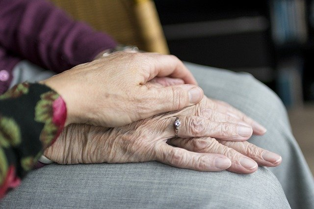 Two women holding hands, one younger hand gently holding an elderly hand
