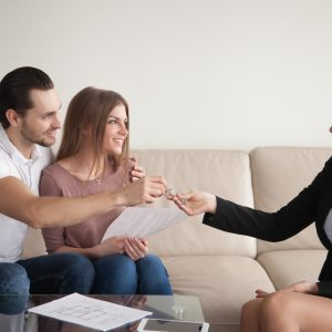 Female realtor giving keys to happy owners of apartment, couple of renters getting key of new home after signing rental agreement, young family starting new happy life in own house
