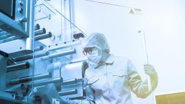 bended caucasian factory worker in blue lab suit work with machine, stand behind glass panel
