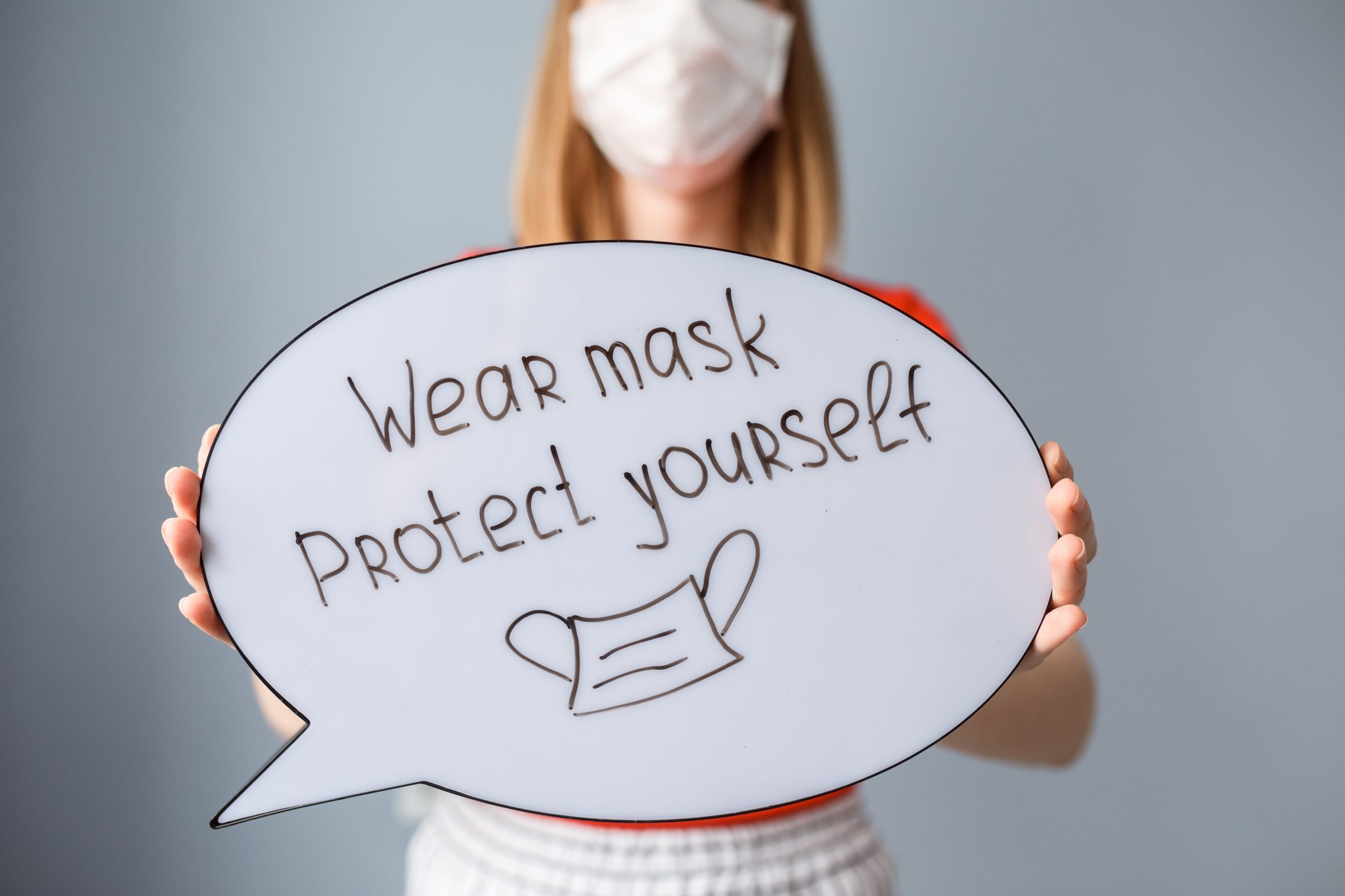 "A whiteboard with handwritten text that reads ""wear a mask, protect yourself"""