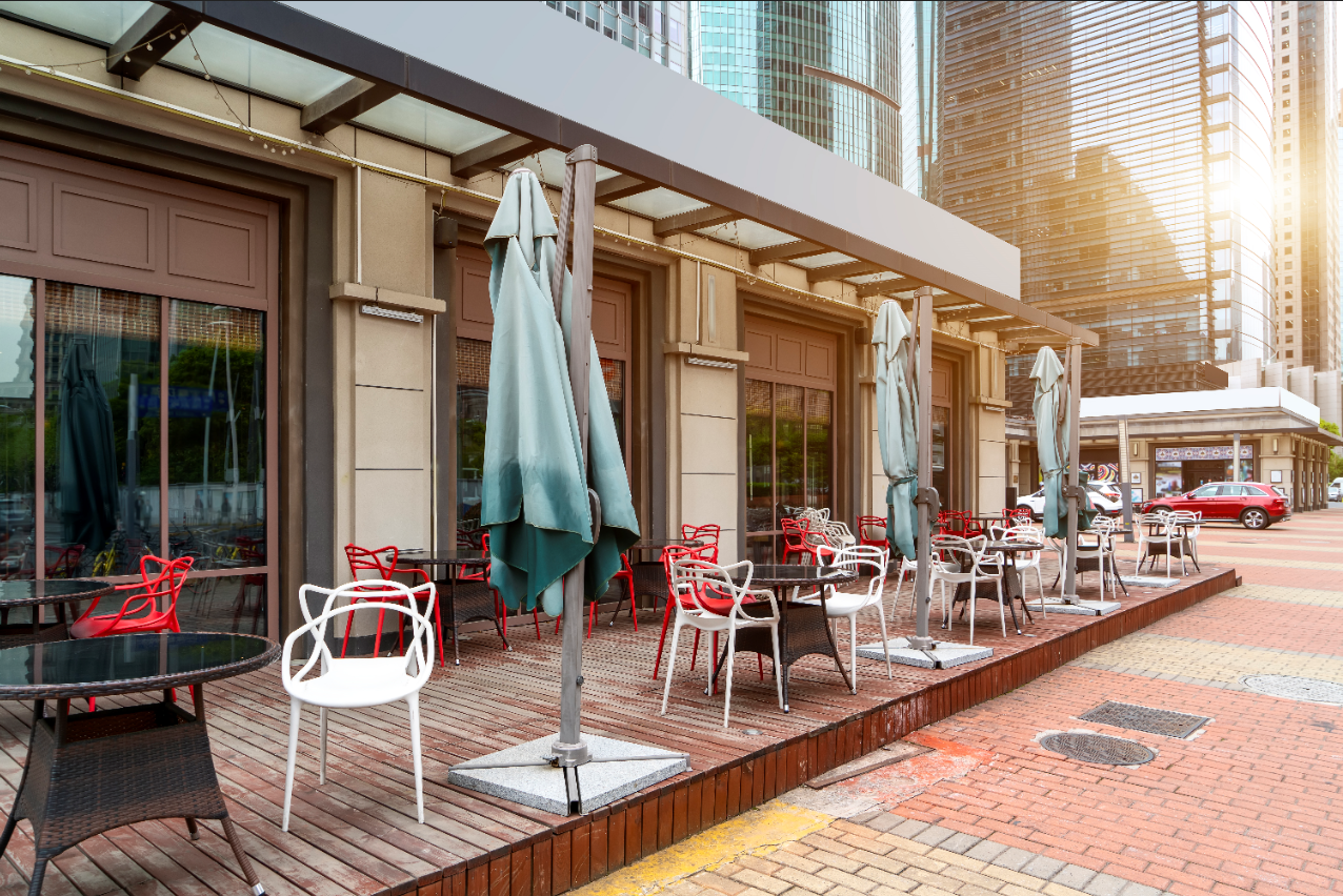 An outdoor restaurant patio with socially distanced chairs and tables