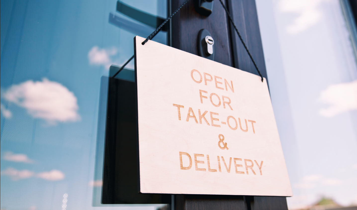 """Wooden sign hanging on a restaurant door with text that reads """"open for take-out and delivery"""""""